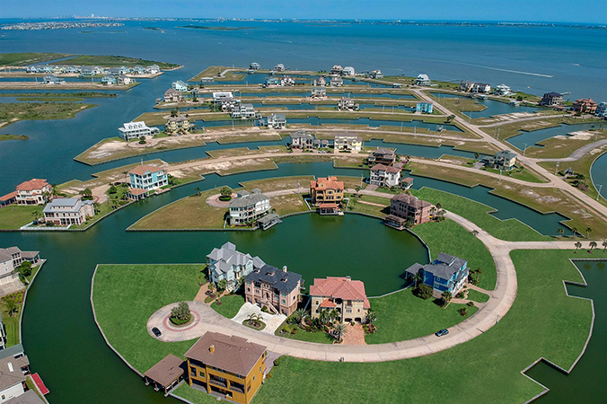Galveston, TX aerial / drone photo of a beautiful home in an ocean cul-de-sac with blue water.